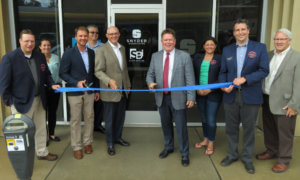 Professionals in front of new office during ribbon cutting
