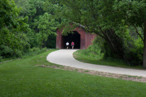 A couple walking onto a covered bridge on the Easter Lake Trail in Polk County.