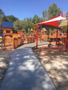 Image of a concrete path leading to handicap accessible playground equipment at the Council Bluffs Dream Playground Reimagined.