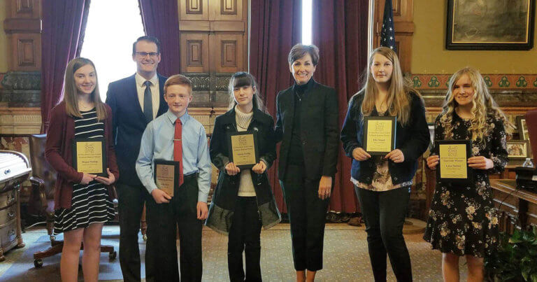 Governor Kim Reynolds and Lt. Governor Adam Gregg gather for a group photo with scholarship award recipients of the 2018 Iowa League of Cities If I Were Mayor Essay Contest during a ceremony at the Iowa State Capitol.