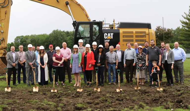 Ames School officials pose for group photo in front of excavator