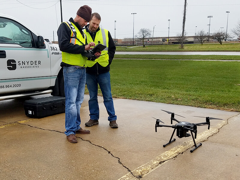 Two survey technicians programming a UAV with a Snyder & Associates work truck behind them.